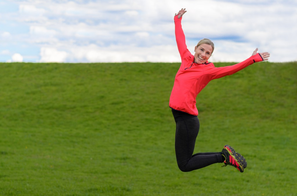 Fit healthy woman jumping for joy viewed midair with outstretched arms and a friendly smile over a green rural field with copy space